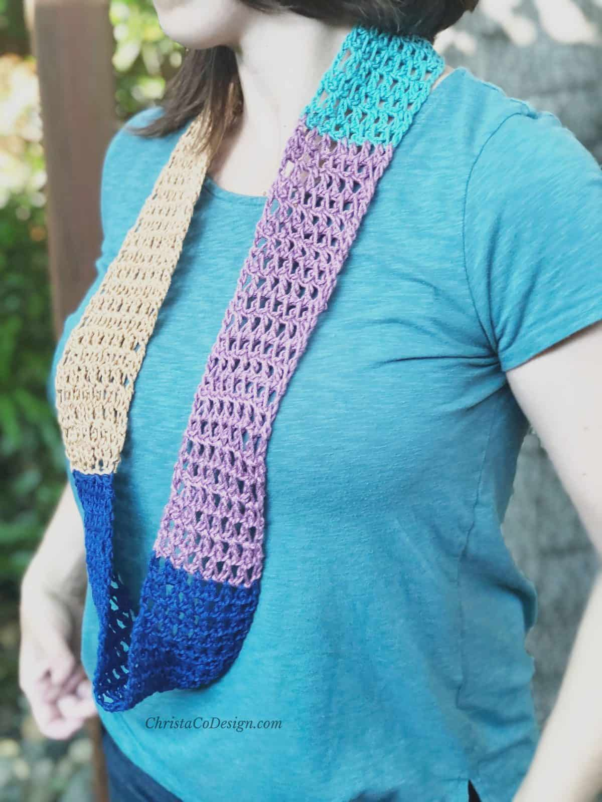 Light and lacy crochet cowl in blue and purple hanging long on woman.