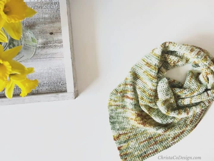 Crochet triangle scarf in hand dyed yarn on table with daisies.