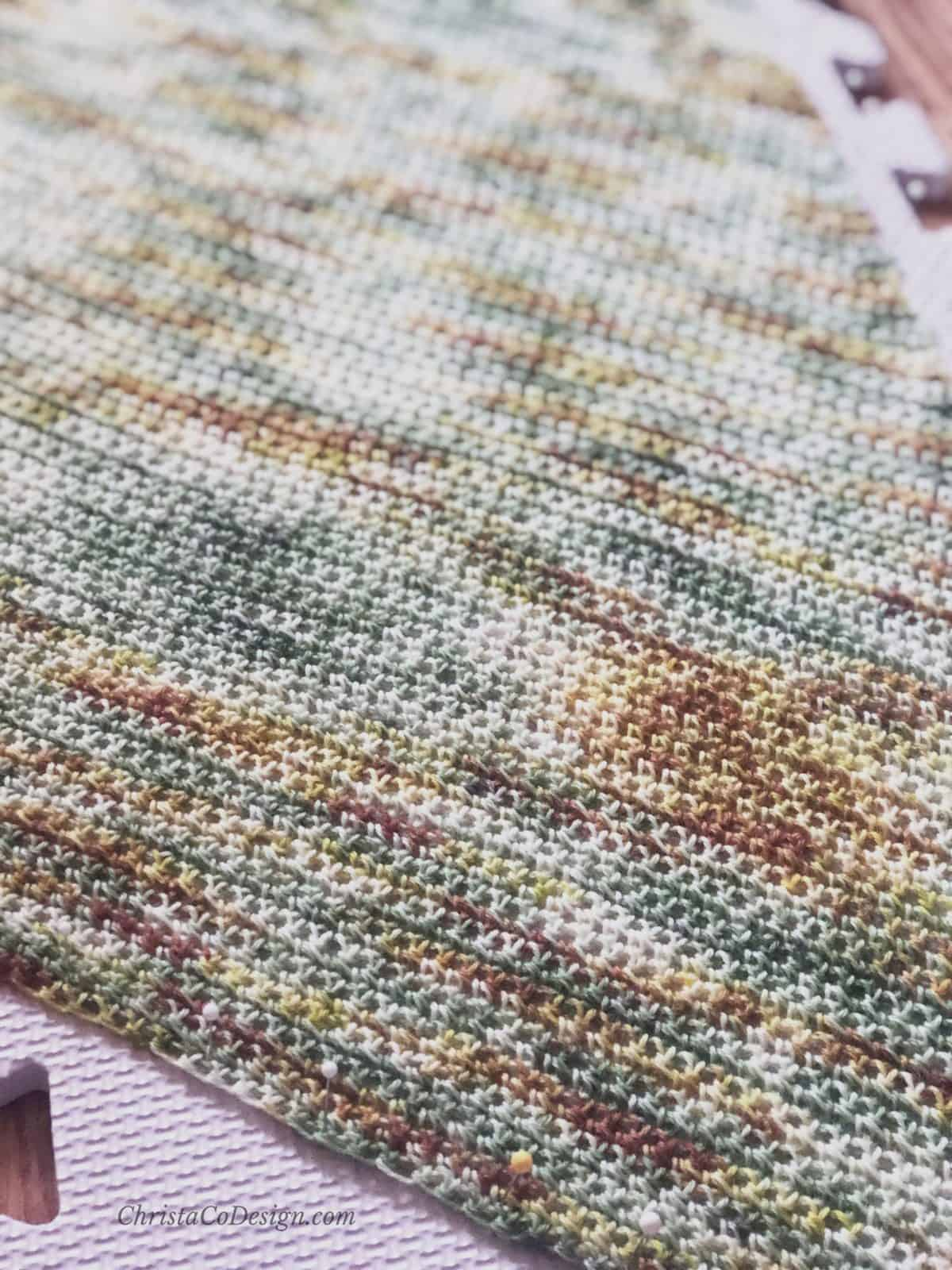 Close up of hand dyed yarn in green and rusts for crochet scarf blocking with pins.