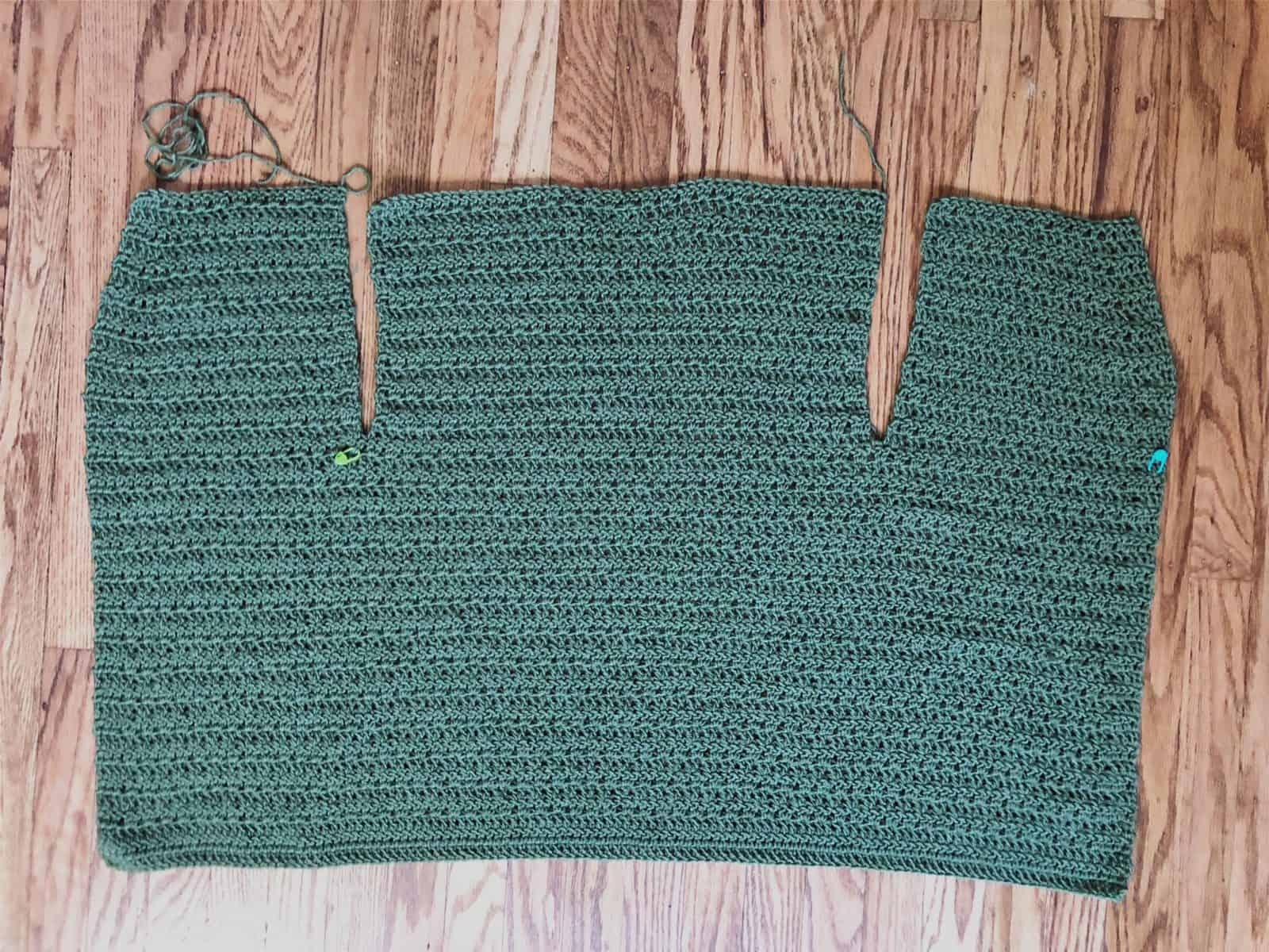 picture of crochet cardigan divided for back and front panels on wood floor