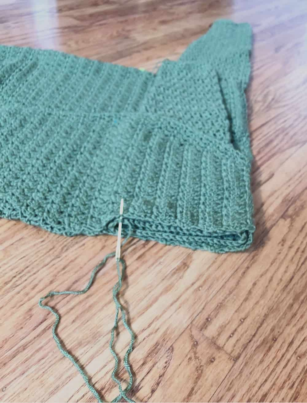 Seaming sleeve to armhole.