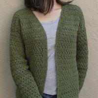 picture of woman in dark green crochet cardigan standing on beige wall