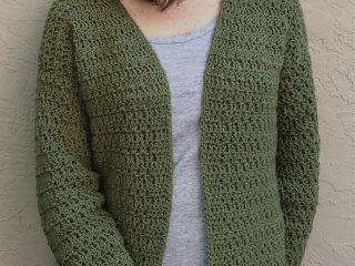 picture of woman in dark green crochet cardigan standing on beige wall