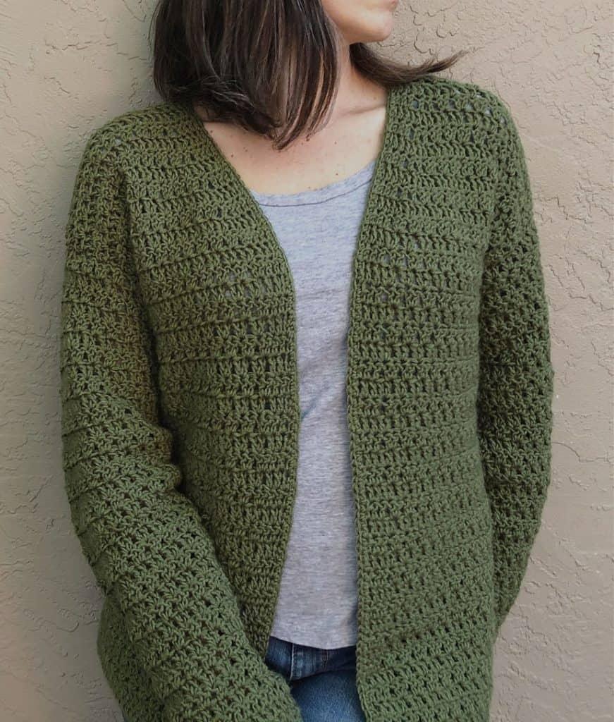 Woman in dark green crochet cardigan standing on beige wall.