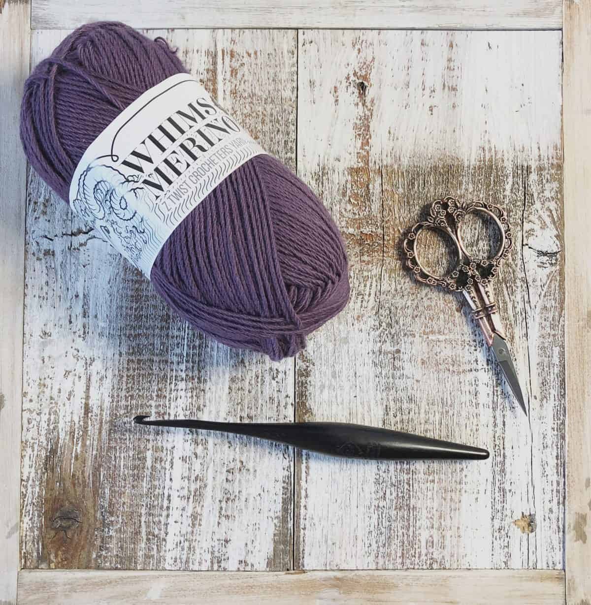 picture of one ball Whims Merino yarn in purple with wood crochet hook and scissors