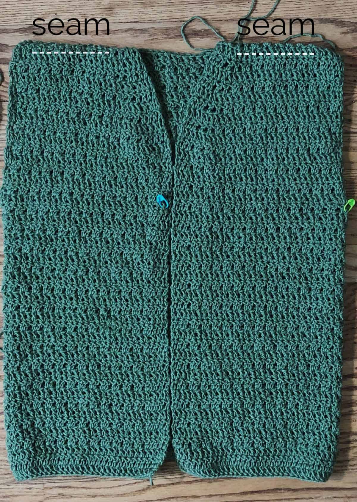 picture of green crochet cardigan with seam labels on shoulders