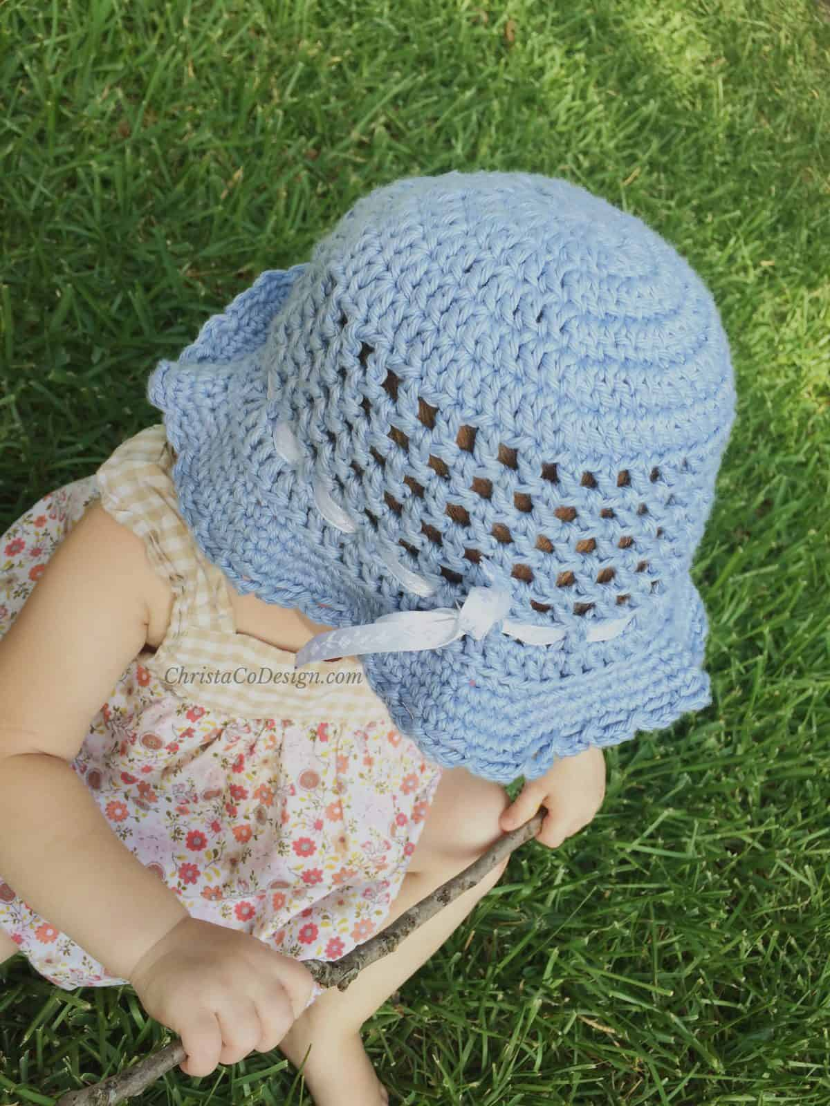 Girl outside wearing blue hat started with a crochet magic circle.