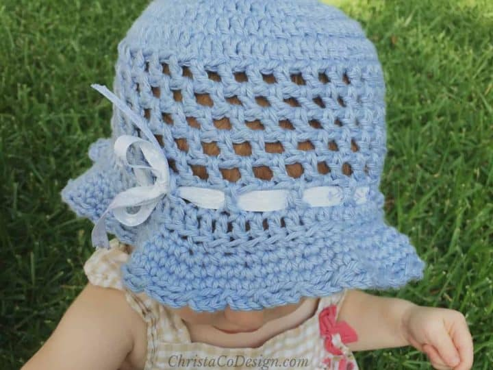 Toddler in blue sun hat with ribbon.