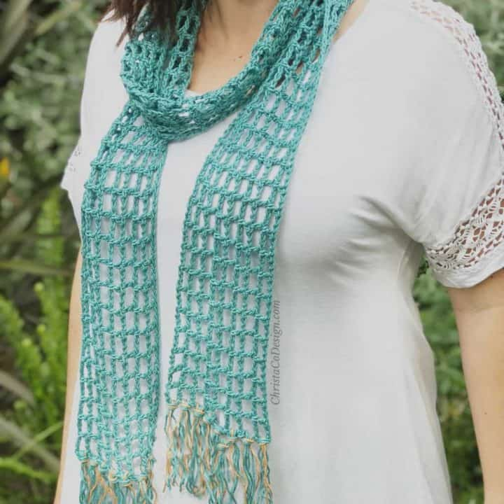 Woman wearing teal lace skinny summer scarf.