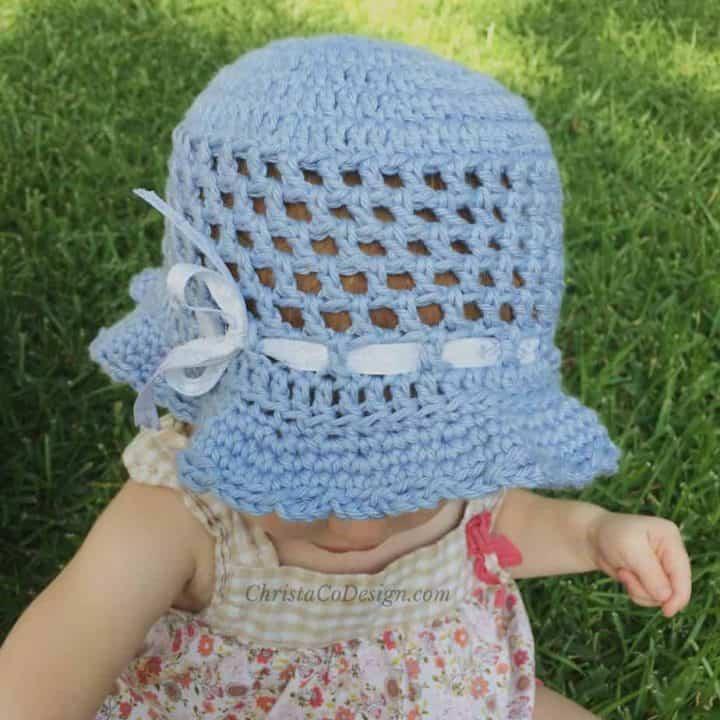 Baby outside in blue crochet sun hat.