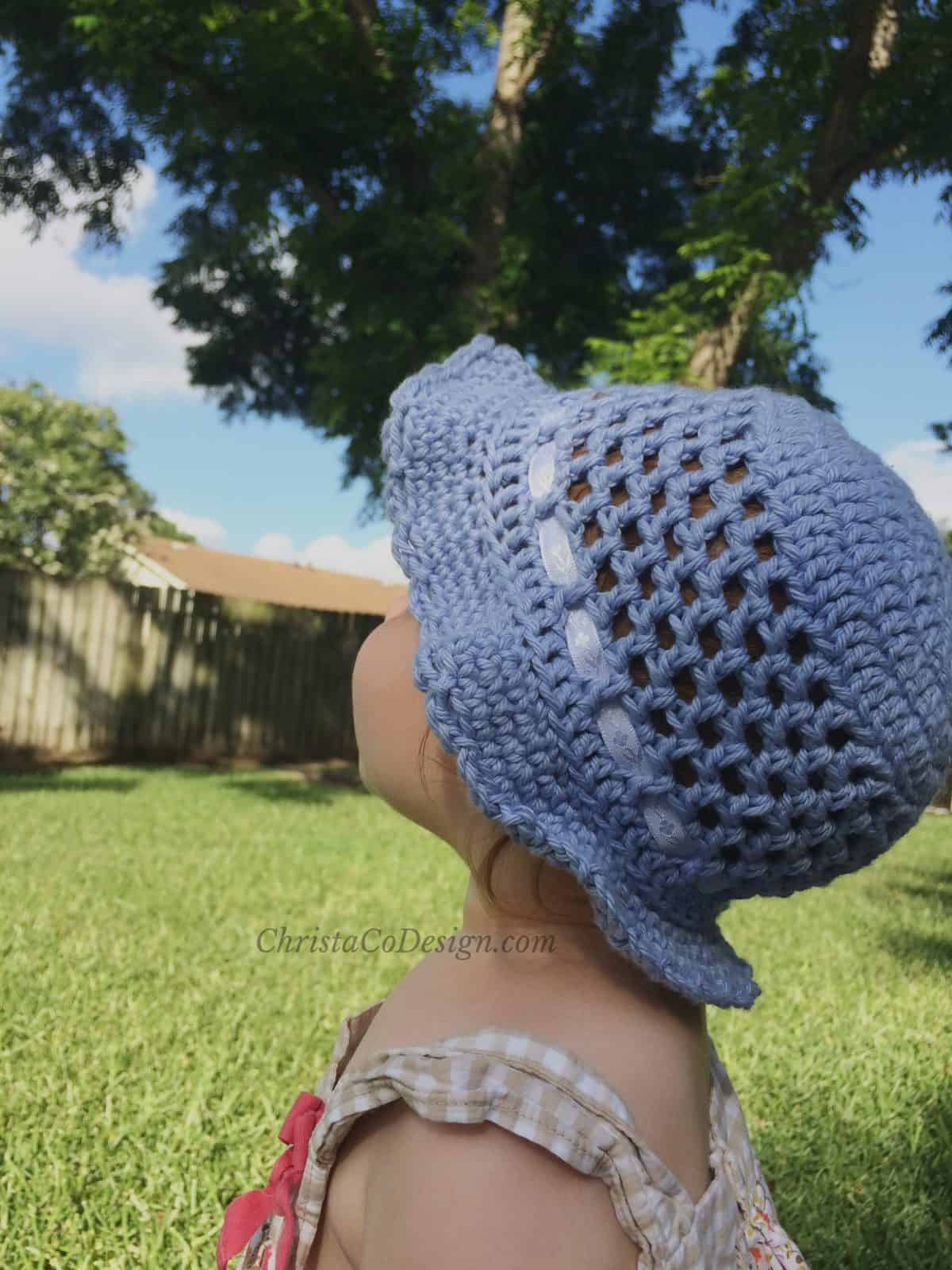 picture of baby outside in toddler sun hat of girl in grass wearing crochet hat