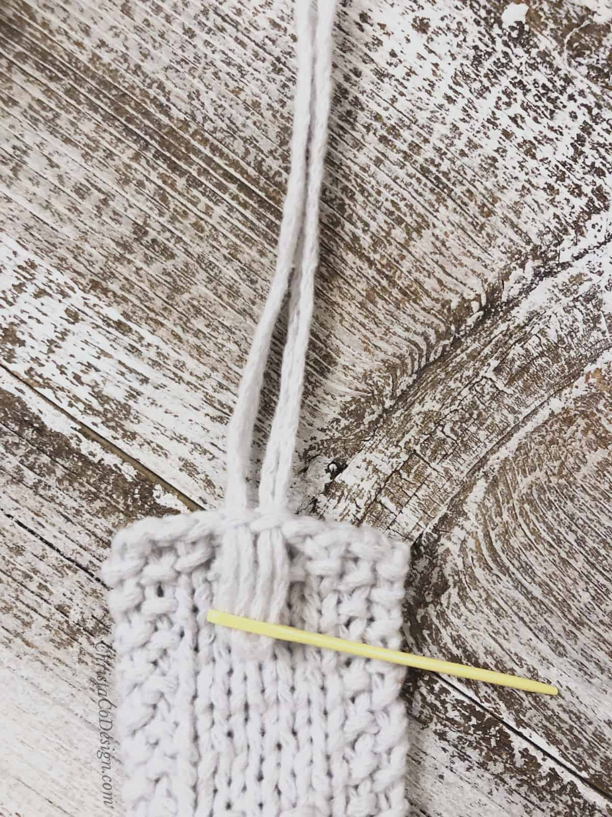 picture of yellow yarn needle threaded with white fringe for knit bookmark