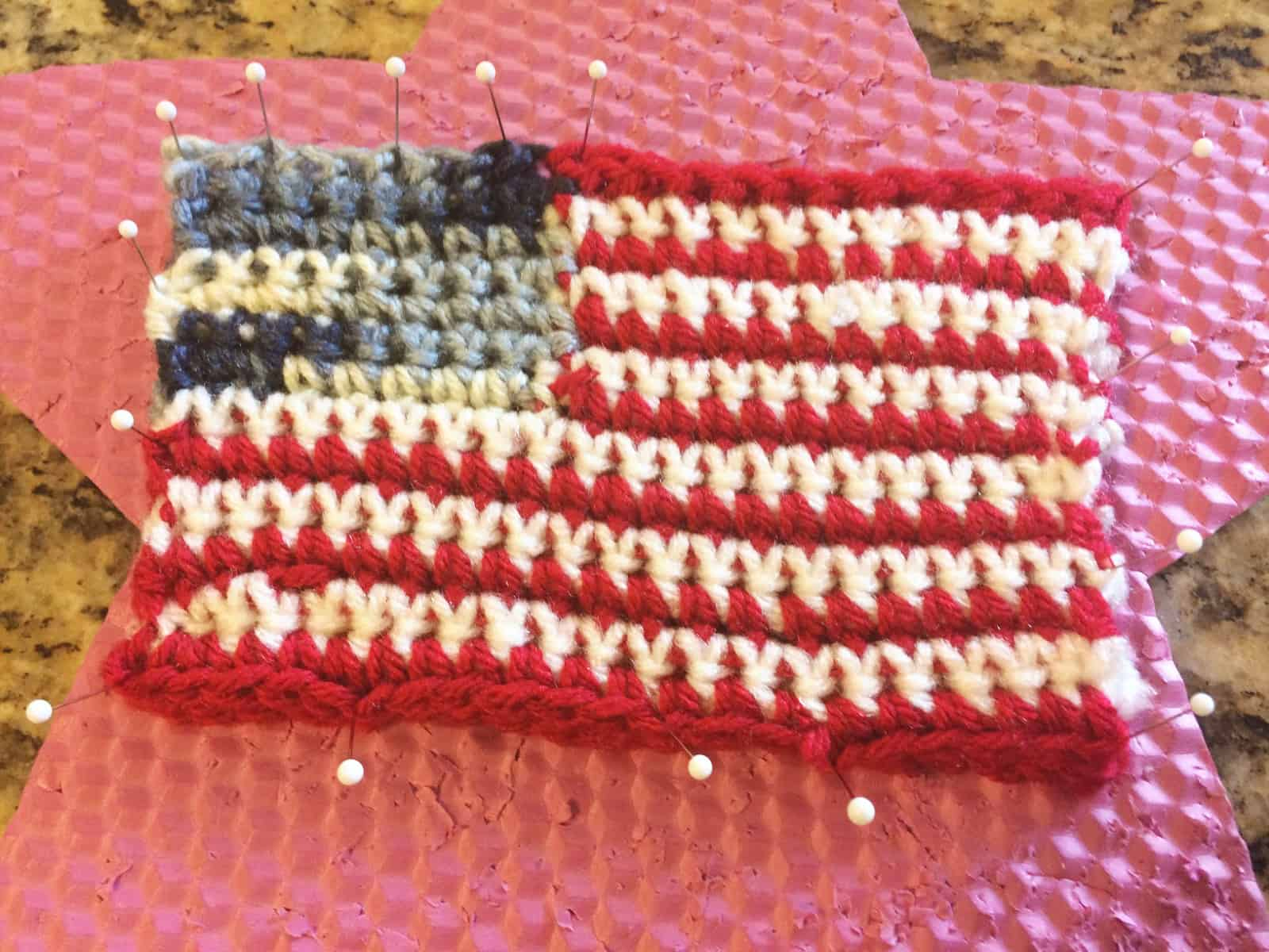 picture of crochet us flag pinned to pin foam for blocking