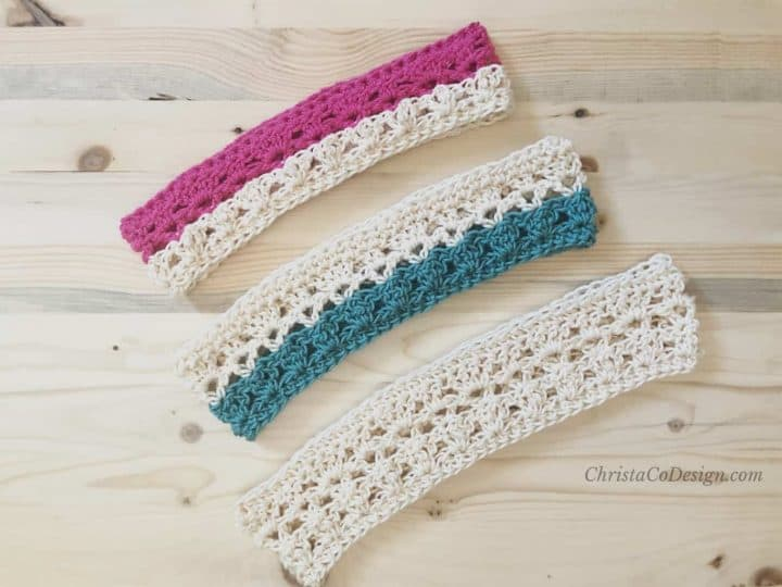 picture of three crochet headbands laid flat in pink, teal and cream