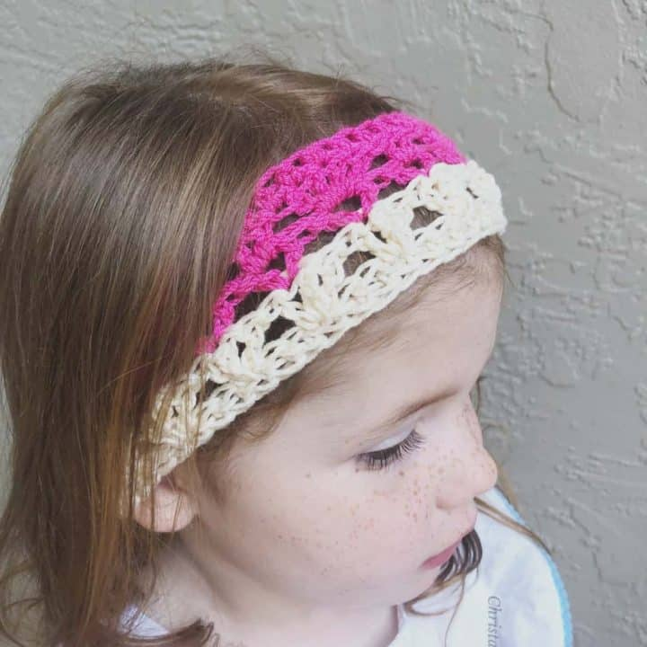 Girl in pink and cream in crochet summer headband pattern free 5 sizes.