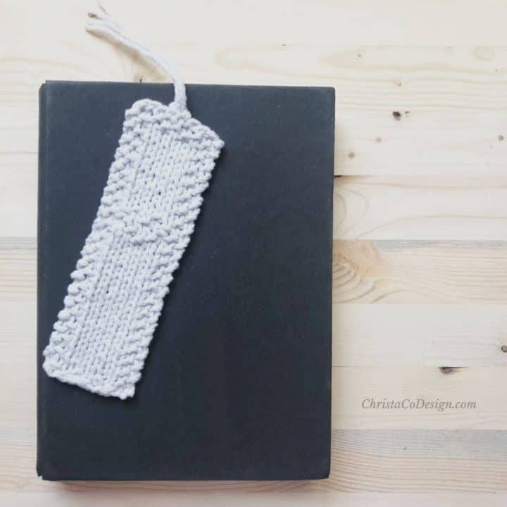 picture of beginner knit bookmark in white with heart detail on black book