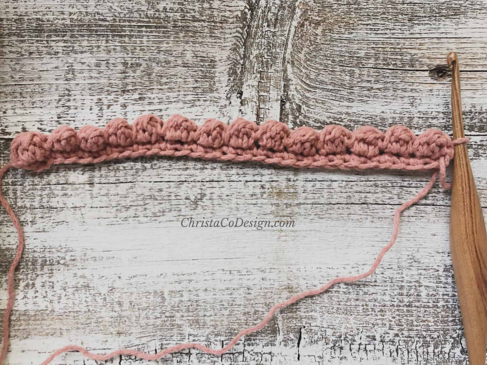 picture of row 2 uneven berry stitch tutorial in pink yarn