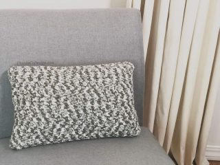 picture of grey and white crochet pillow on grey chair