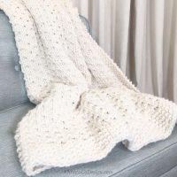picture of Bella vita easy blanket beginner knitting in cream yarn on blue chair