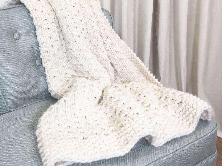 Bella vita easy knit blanket beginner knitting pattern in cream yarn on blue chair.