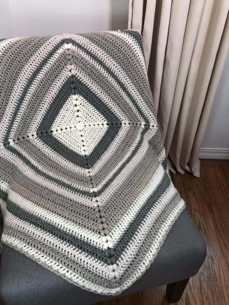 Square crochet blanket draped on chair.