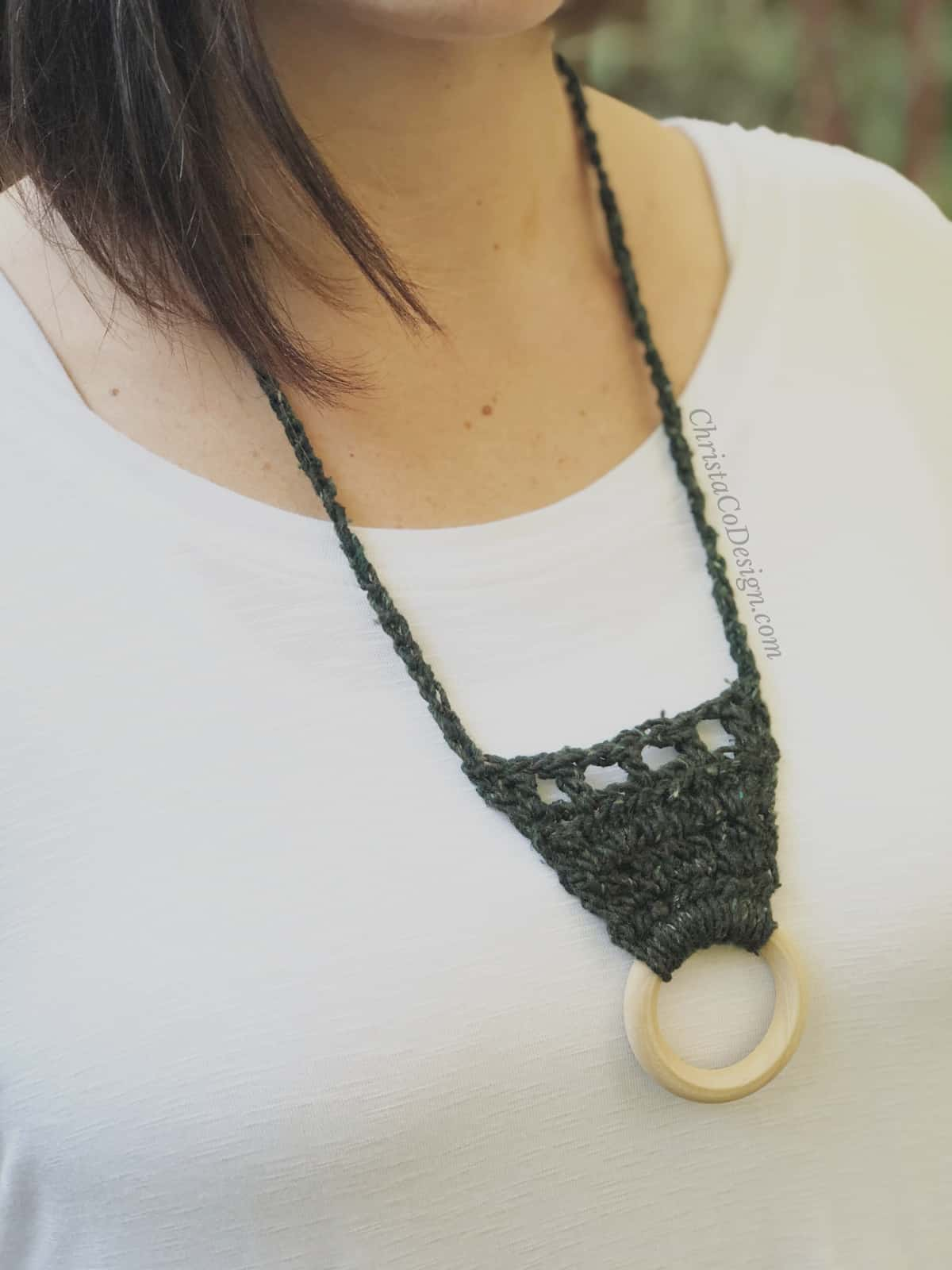 picture of dark green easy crochet necklace up close with wood ring at center on woman's white shirt