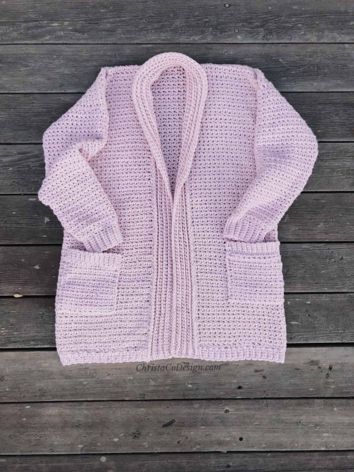 picture of cozy crochet cardigan in pink laid flat on boards