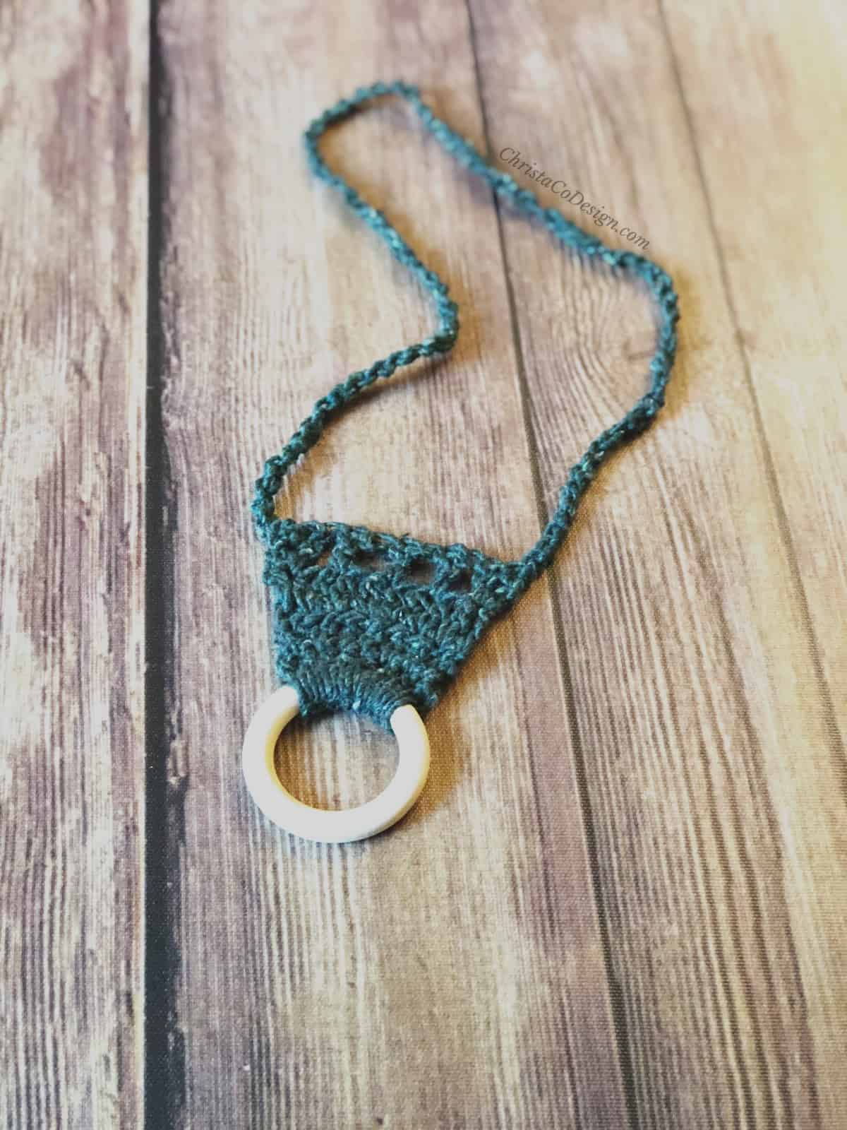 picture of easy crochet nursing necklace in dark green yarn with pale maple wood ring as pendant