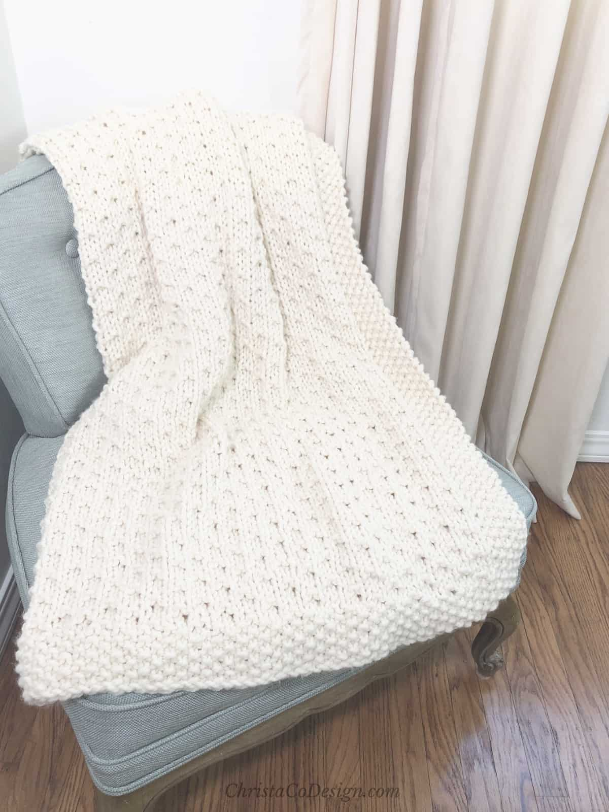 picture of Bella vita easy blanket beginner knitting in cream yarn on blue chair