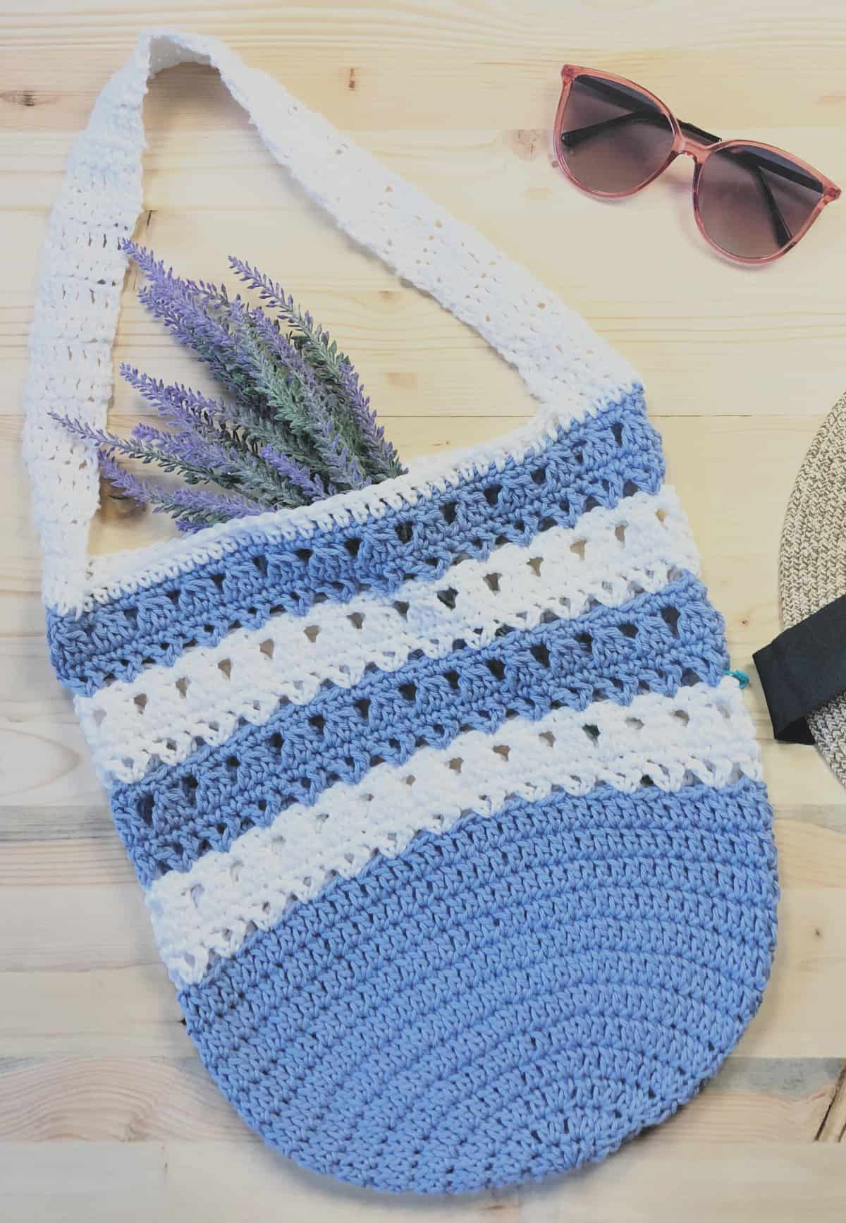 Free crochet tote bag pattern in blues and whites flat with lavender and sunglasses.