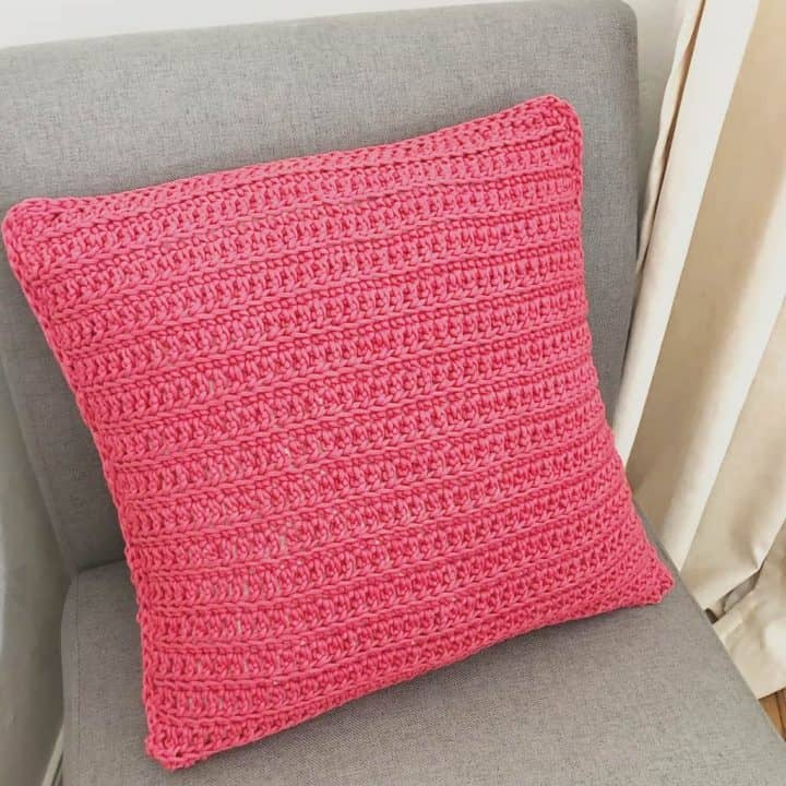 picture of red crochet pillow with envelope closure on grey chair