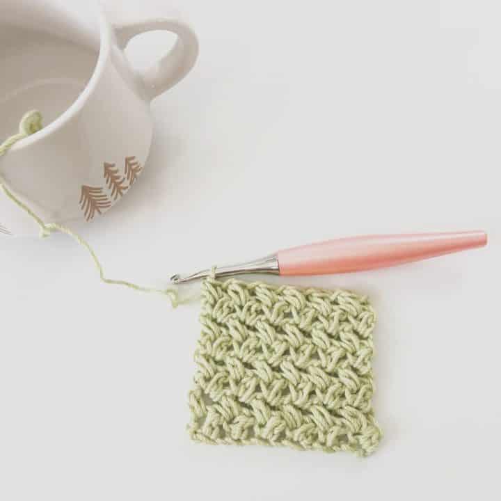 Lime green crochet mini bean stitch crochet swatch on peach hook.