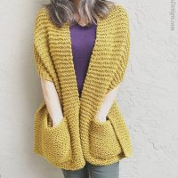 picture of woman wrapped in honey colored knit pocket shawl pattern
