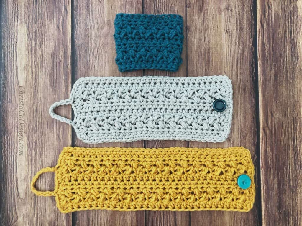 Three crochet cup cozies, one to go in blue on top, regular size cup cozy in grey with button and oversized mug cozy on bottom.