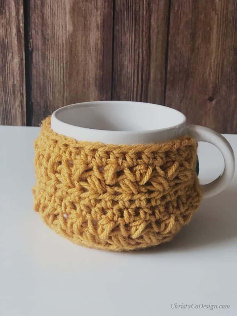 Crochet cup cozy on oversized coffee mug in mustard yellow.