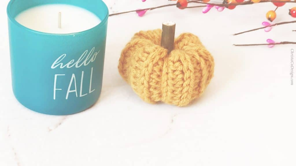 Small crochet pumpkin with ribbing and blue fall candle.