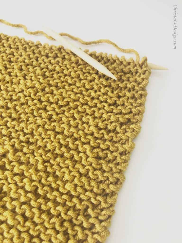 Mustard yellow garter stitch shawl on knitting needles.