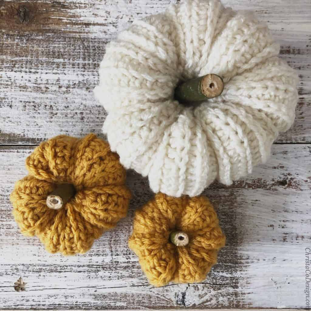 Top down view of crochet pumpkins with natural stems in white and mustard.