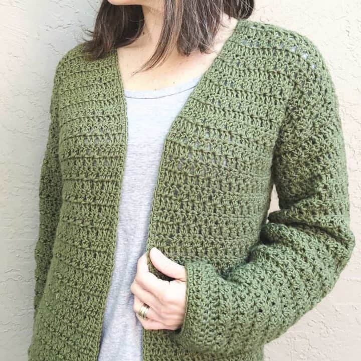 Green crochet cardigan on woman.