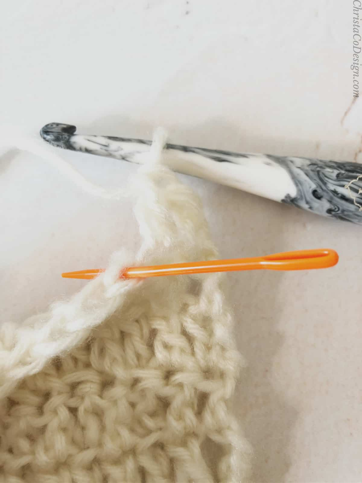 picture of orange yarn needle in blo of dc stitch
