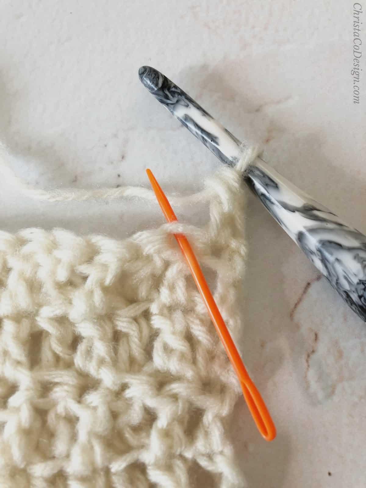 picture of orange yarn needle through front loop of double crochet
