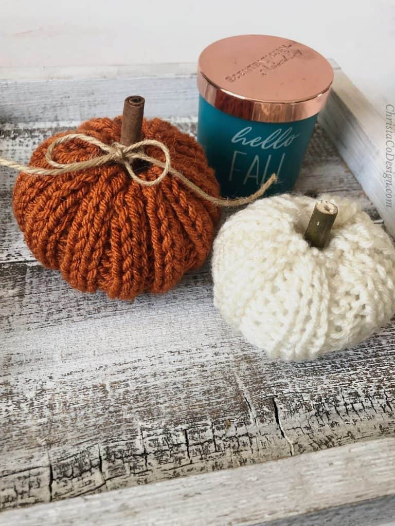 Two knit pumpkins with cinnamons stitch stems and fall candle.