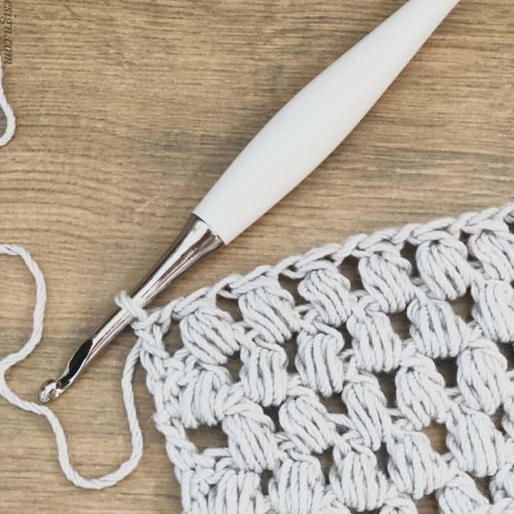 picture of crochet pineapple cluster stitch swatch in grey with white crochet hook