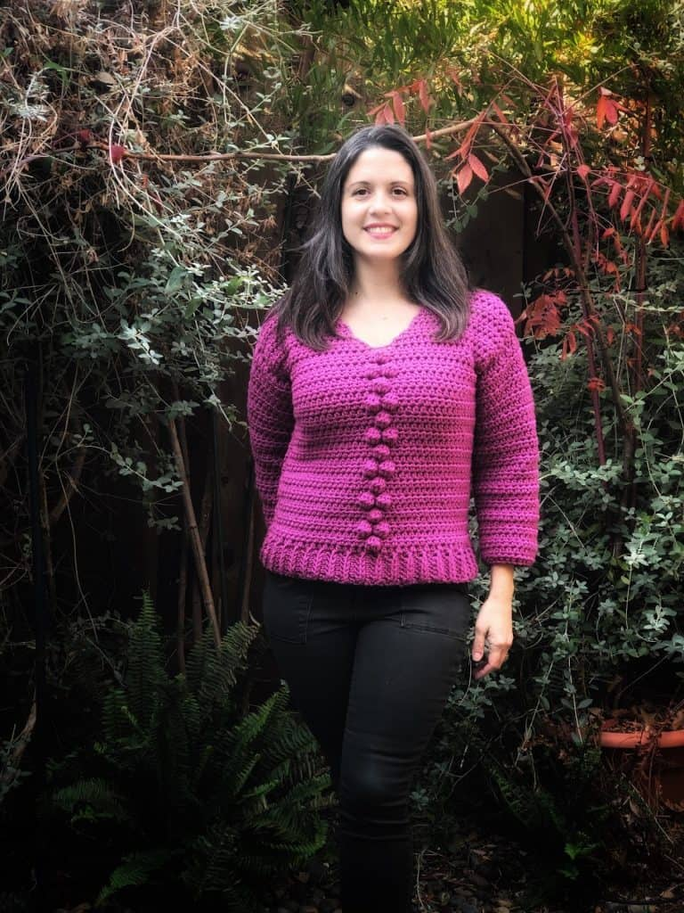 picture of woman in crochet bobble sweater in pink outside
