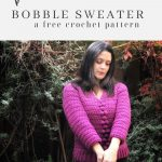A woman holds her arms in front, showing the bracelet length sleeves and looking down, she's wearing a pink crochet sweater with bobbles on the front and v-neck.