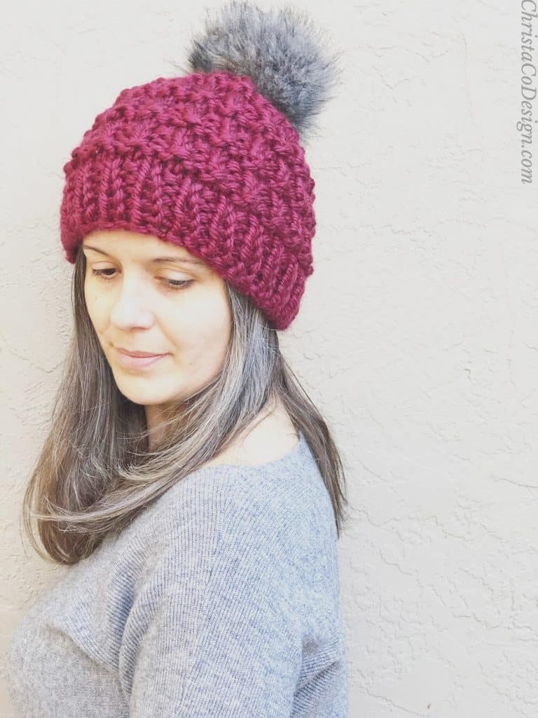 picture of woman in maroon knit hat with Pom Pom