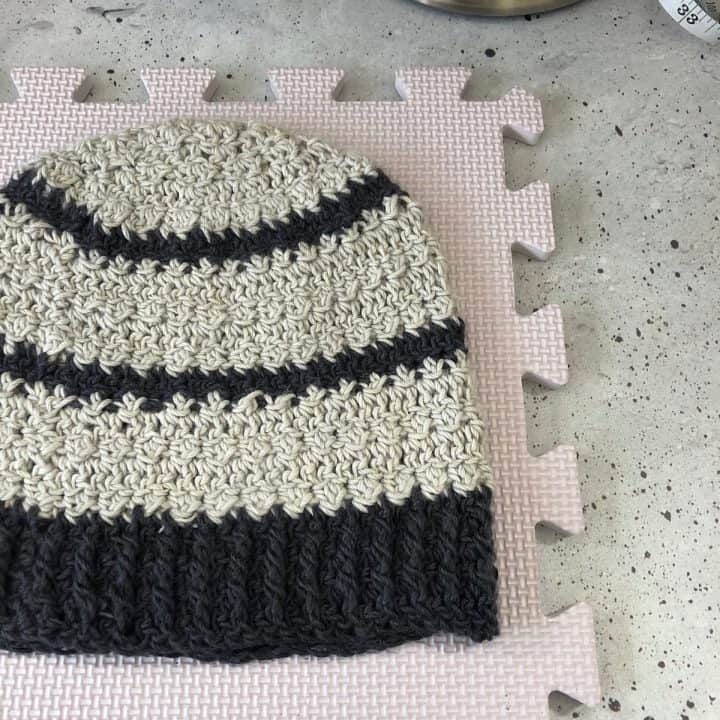 A grey and black crochet hat laid flat for blocking on board.