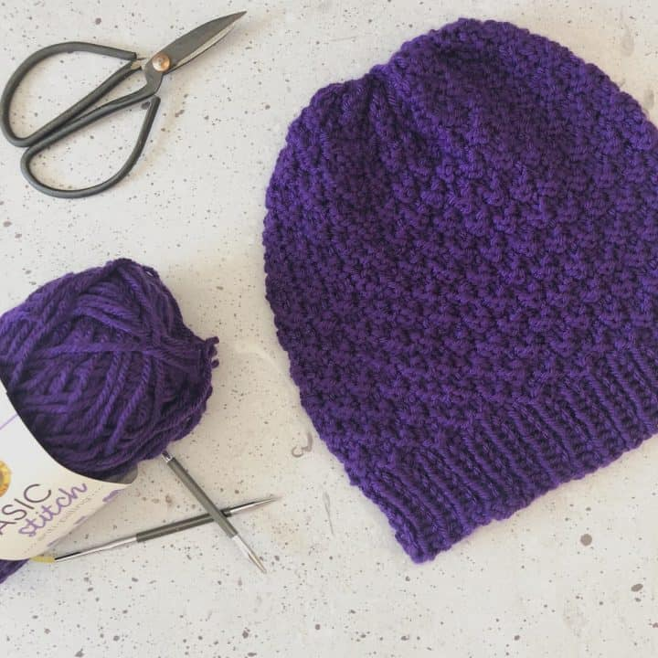 The purple knit hat is laid flat with yarn, needle and scissors.