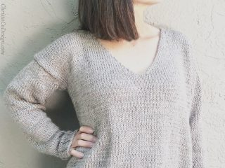 Woman turned in beige v-neck knit sweater.