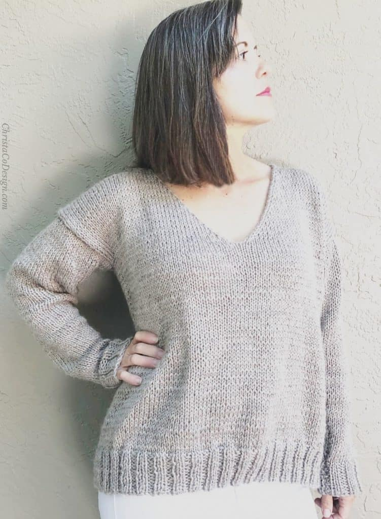 Woman turned in beige v-neck knit sweater.